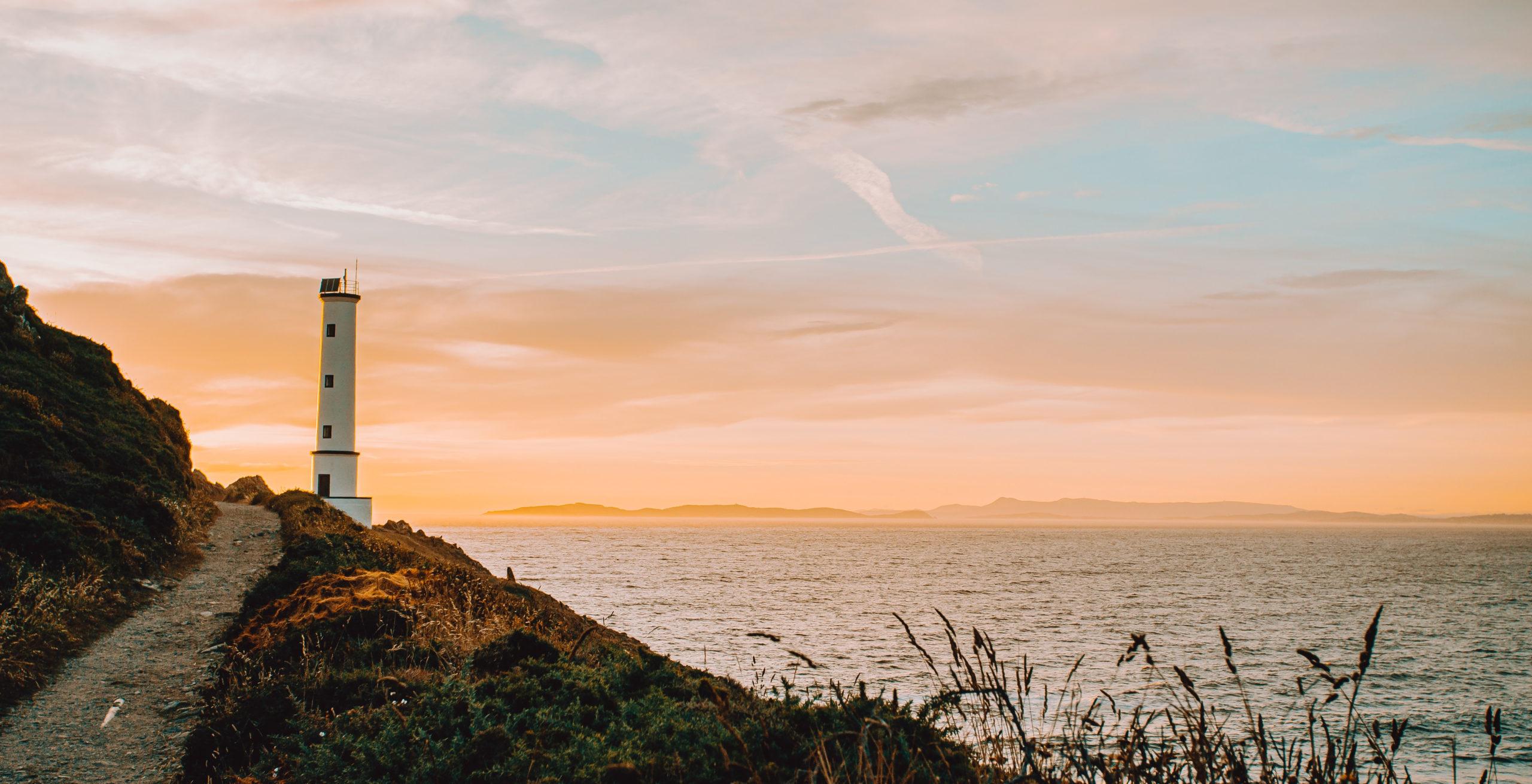 Weg zum Leuchtturm am Meer mit sanftem orangenem Himmellicht
